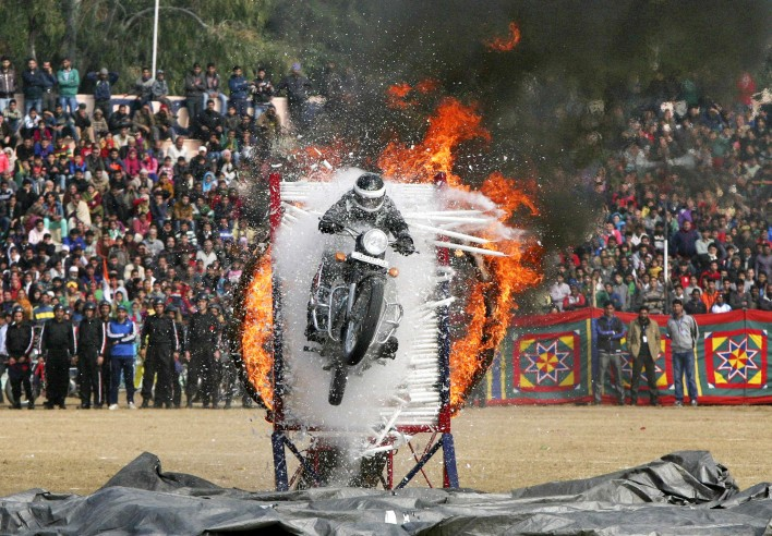 An Indian policeman performs a stunt on his motorcycle during the Republic Day parade in Jammu January 26, 2015. India celebrated its 66th Republic Day on Monday. REUTERS/Mukesh Gupta (INDIAN-ADMINISTERED KASHMIR - Tags: POLITICS ANNIVERSARY)